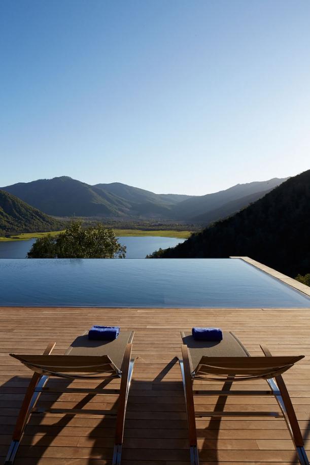 Hladina bazénu zabudovaného do dřevěné terasy splývá s horizontem jezera Humedal de Millahue v pozadí.