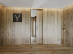 Posuvné dveře a bezobložková pouzdra BELPORT Bezobložkové pouzdro BELPORT s dveřním křídlem sladěném s obkladem stěny v dýhované povrchové úpravě.